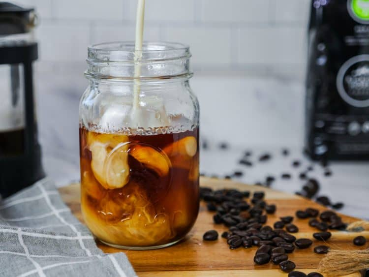 Soy Milk being poured into cold brew coffee in mason jar
