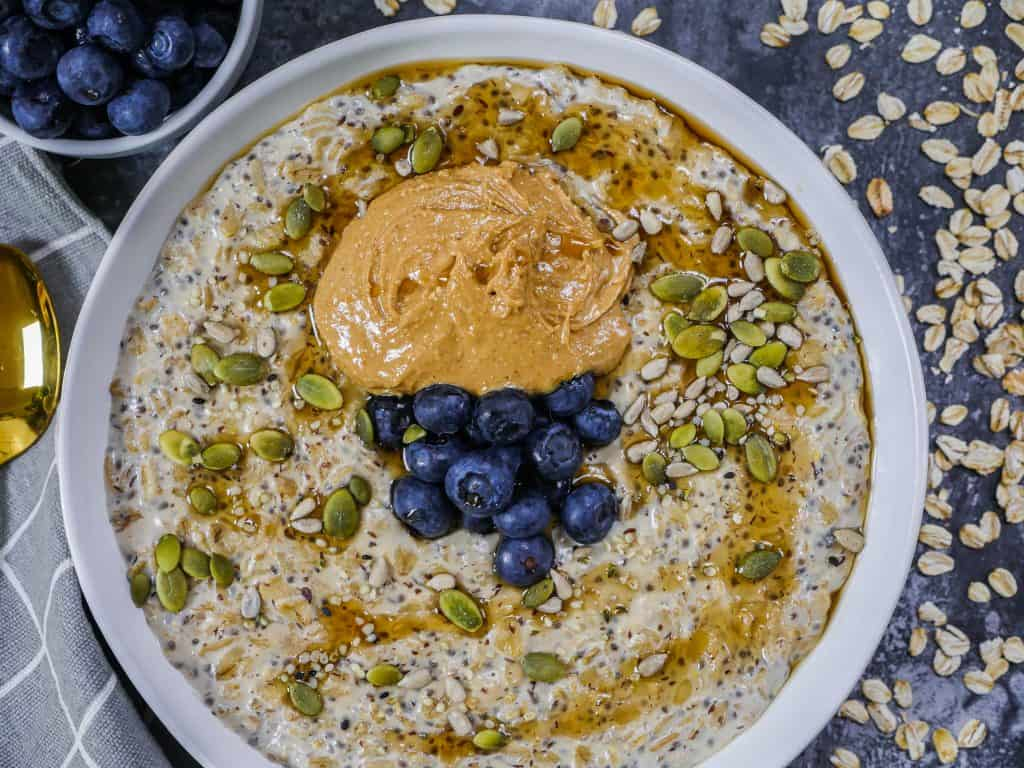 Porridge in a bowl with peanut butter blueberries and pumpkin seeds