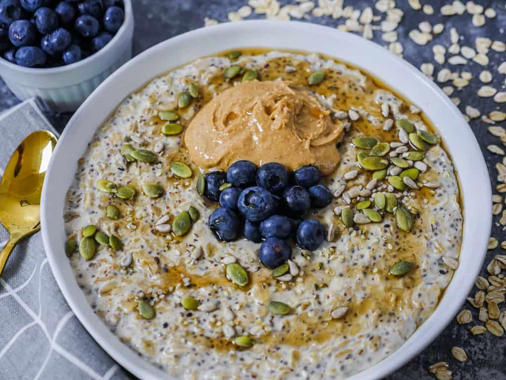 Easy Protein Porridge Recipe with blueberries, peanut butter and pumpkin seeds