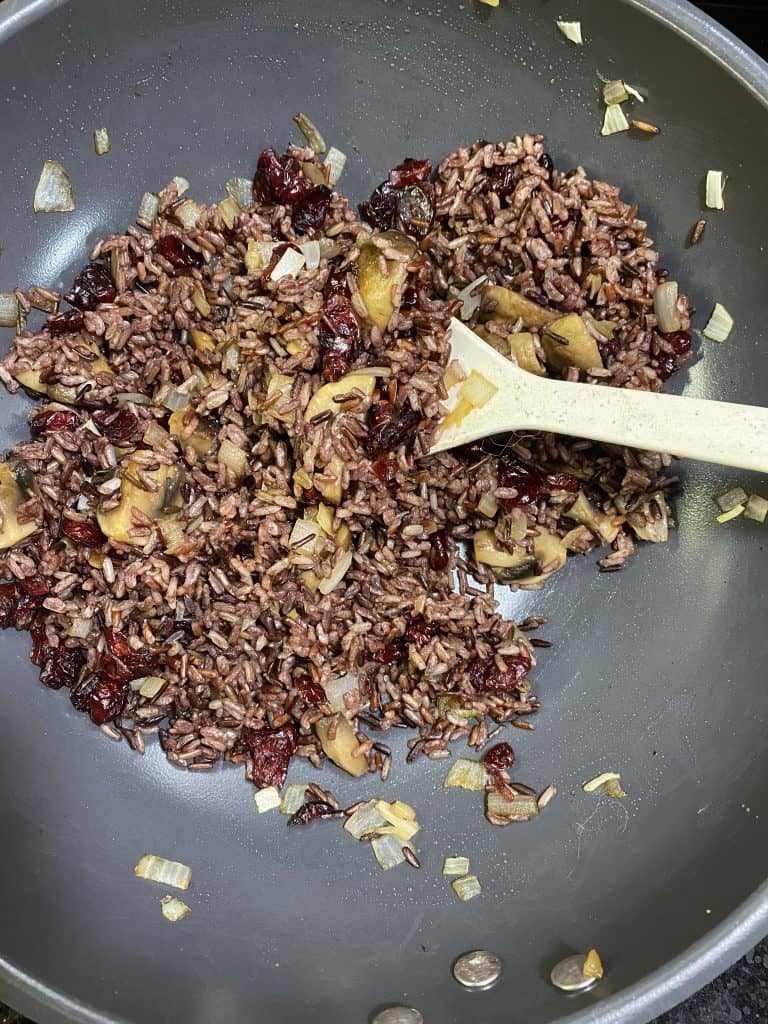 Wild rice blend with mushrooms and onions for loaded sweet potato recipe in a fry pan
