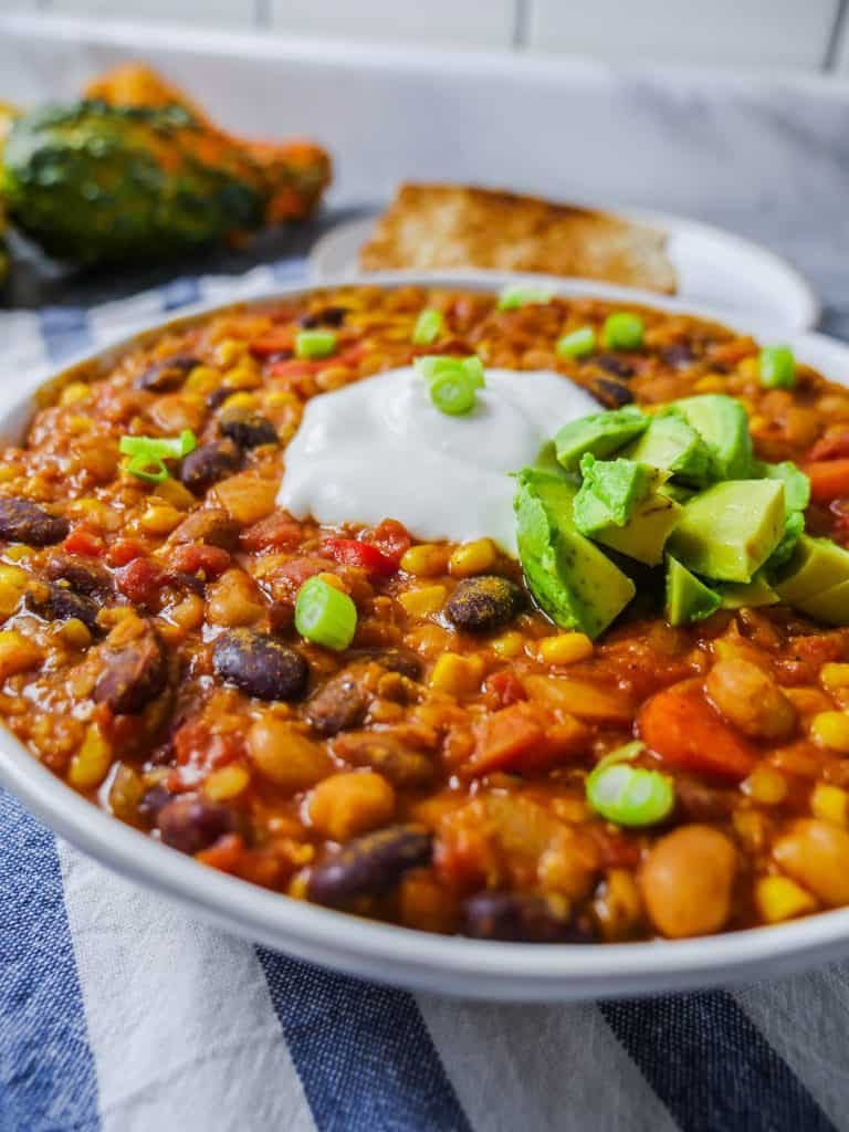 Vegan chili recipe topped with sour cream and avocados and a side of toast